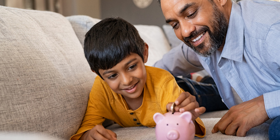 father and son put money in piggy bank