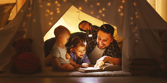 Father reading to young children in an indoor play tent