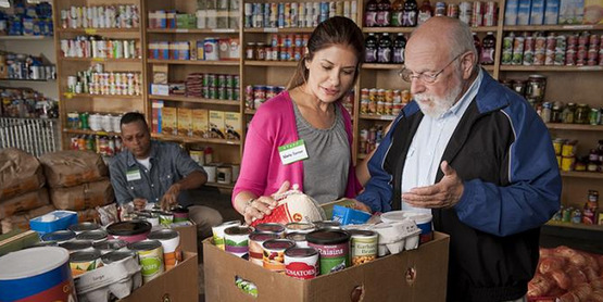 A food pantry staff member helps a client with his selections.