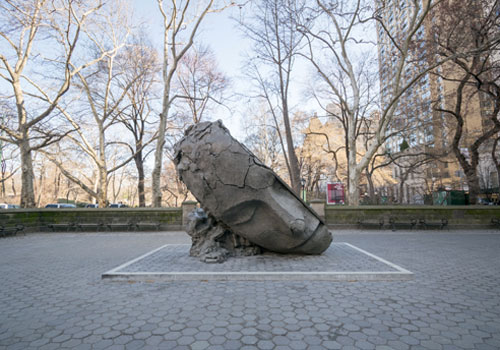 Sculpture of a tilted head at entrance to Central Park