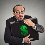 man hugging briefcase filled with money