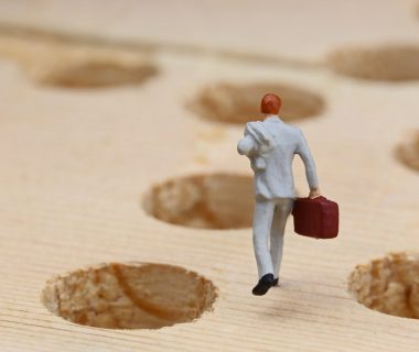 businessman navigating landscape full of holes