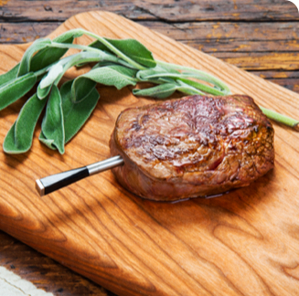 A meat thermometer takes a reading of a steak.