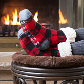 Someone rests their feet in front of a fire, wearing plaid socks with plush lining