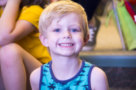 A young patron smiles while waiting for storytime to begin