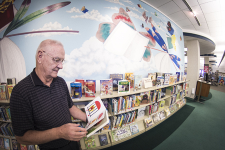 A patron reads in front of the mural at the entrance to the Children's Department