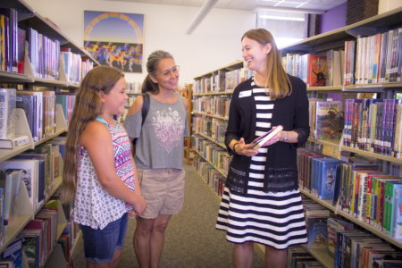 Amanda assists two patrons in the Children's area