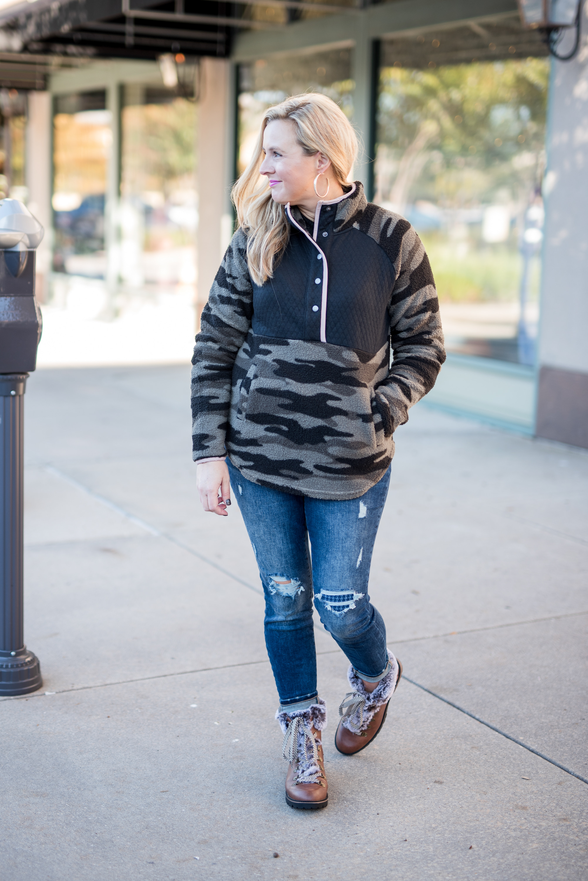 Maurice's Clothing by popular Houston fashion blog, Fancy Ashley: image of a woman wearing a Maurice's camo fleece pullover, distressed denim, and brown fur trimmed combat boots.