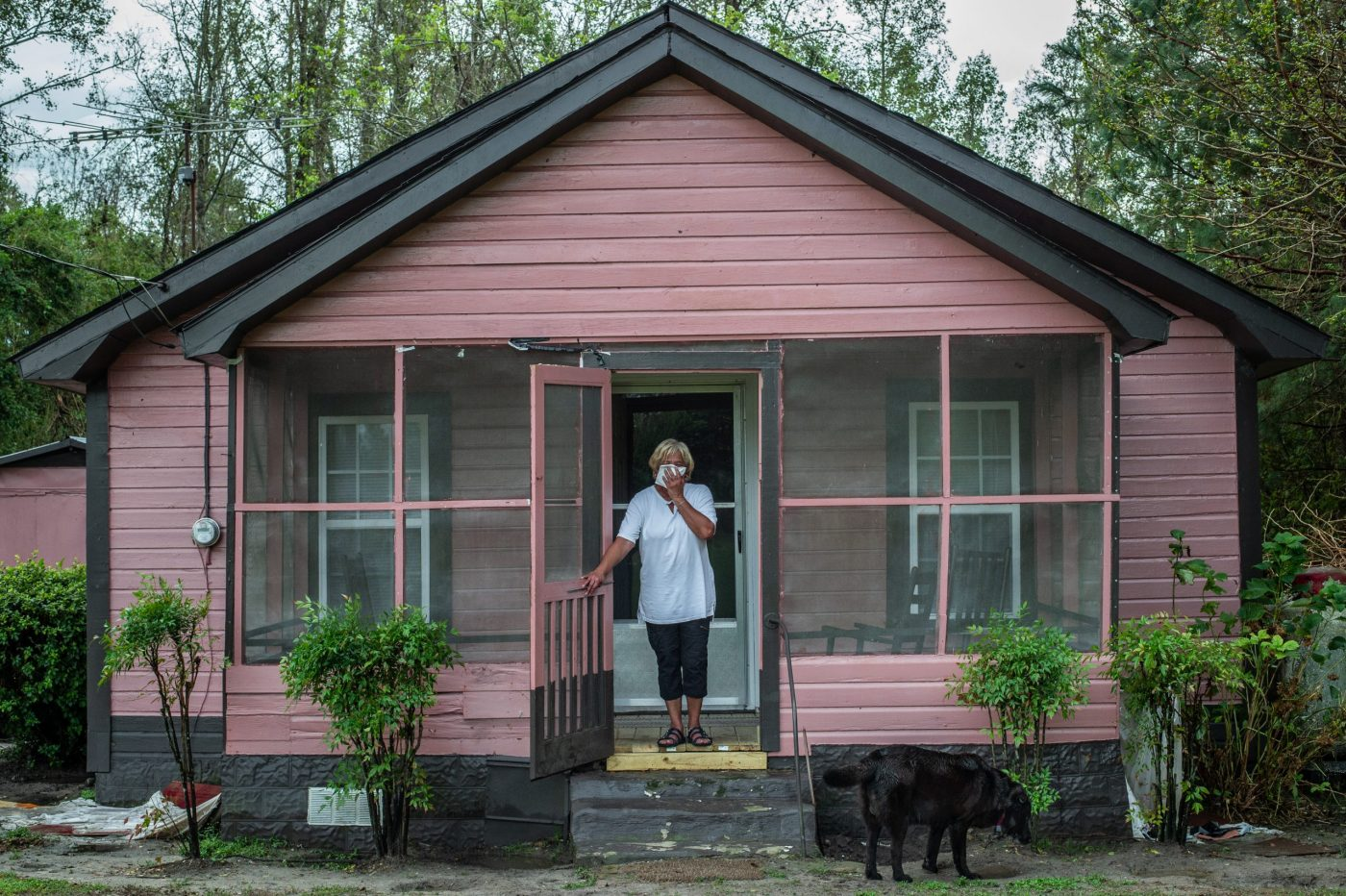 Vertical explainer photo 3 - Activist Elsie Herring, stands on the porch of her family home, holding a handkerchief over her mouth to filter out manure being sprayed on the field next door / Photo Credit: Jo-Anne McArthur / We Animals