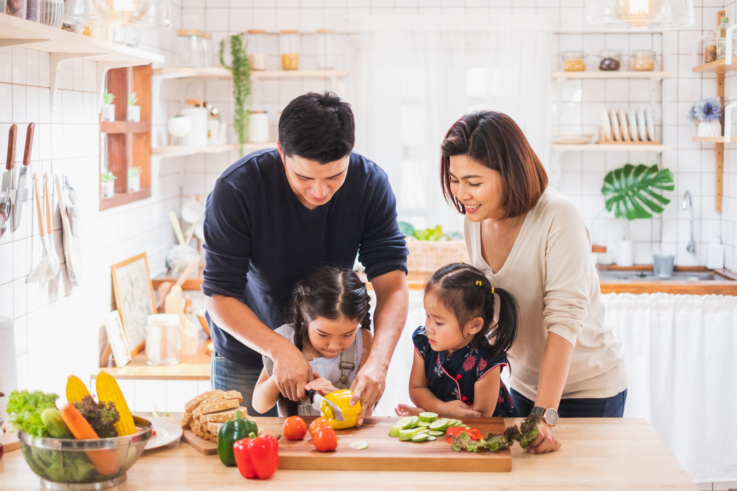 Family cutting vegetables together.