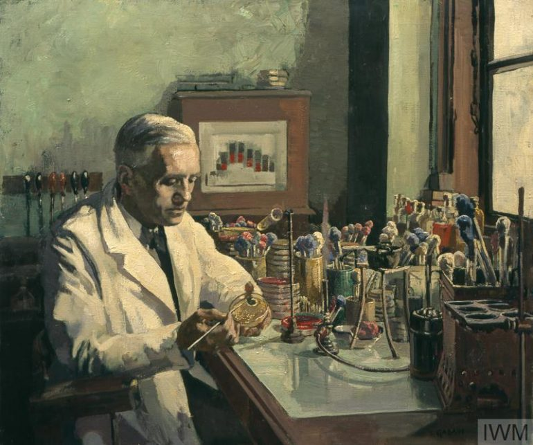 A portrait of Alexander Fleming, wearing a white coat, at work at a desk inside a laboratory. An array of scientific equipment is placed on the surface of the desk and there is a window to the right of the composition.