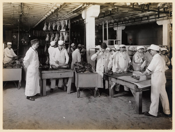 Men in white coats inspecting food products
