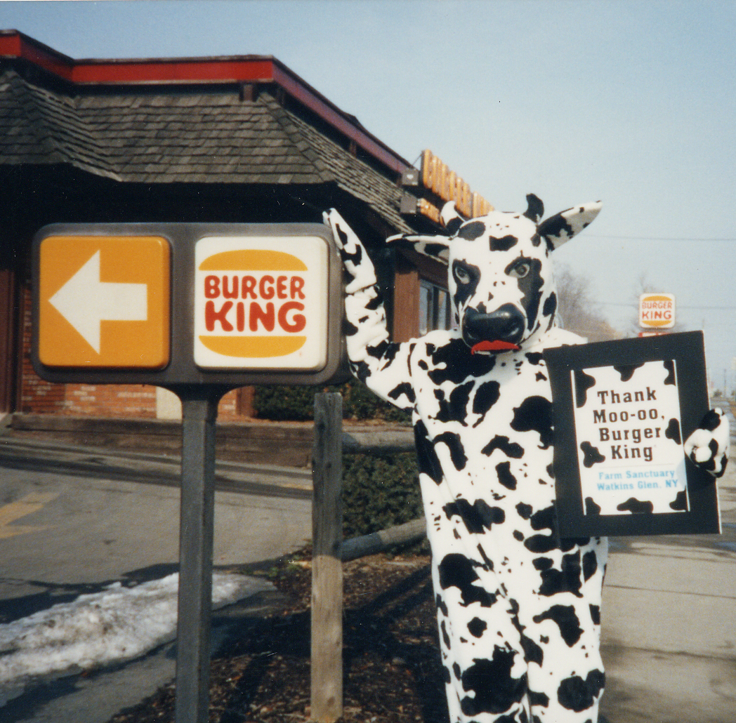 "Person stands outside of the Watkins Glen, NY Burger King with a sign that reads ""Thank Moo-oo, Burger King"""