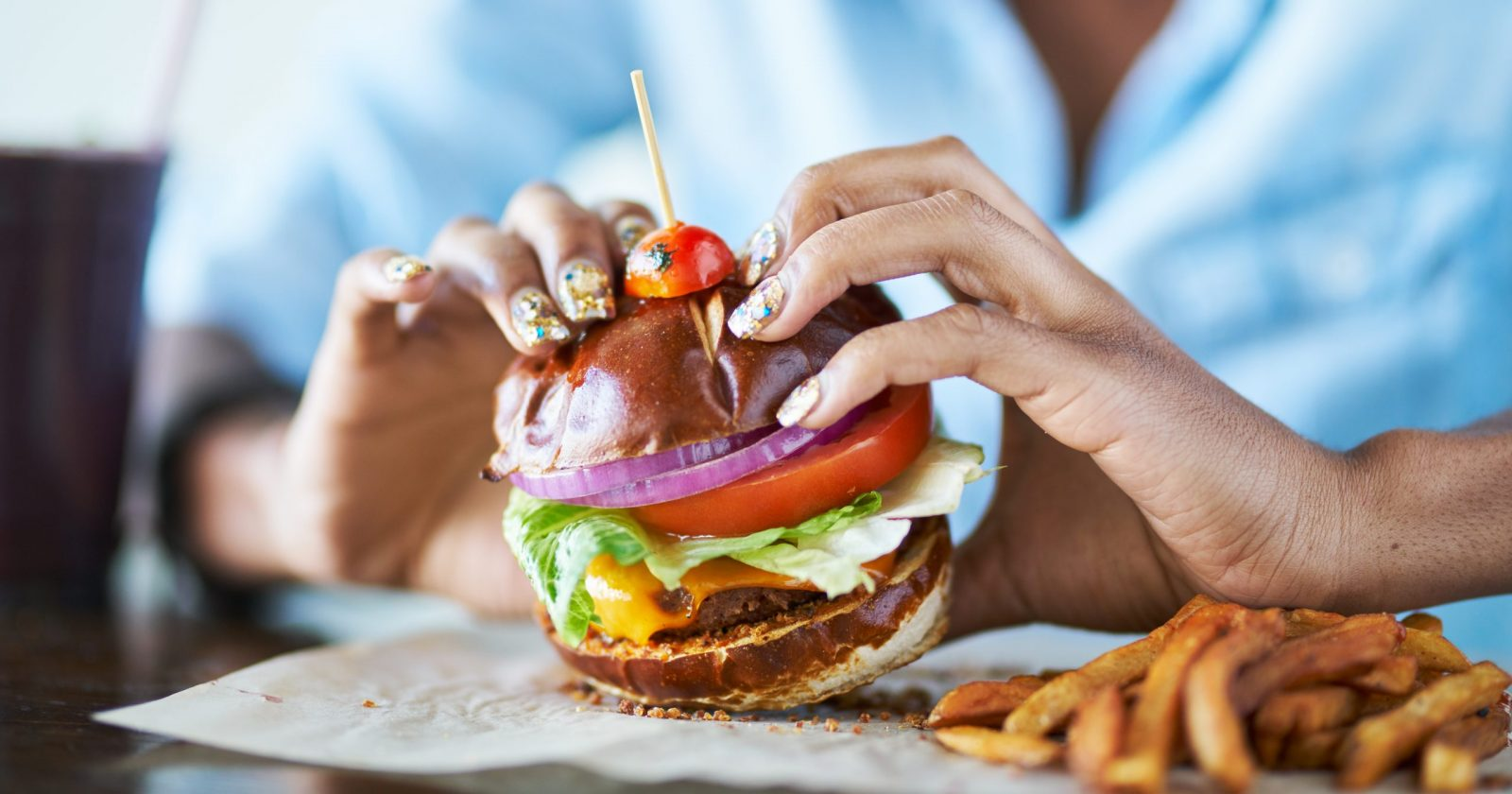 A woman going to pick up a vegan burger at a restaurant / Photo Credit: Joshua Resnick, Shutterstock
