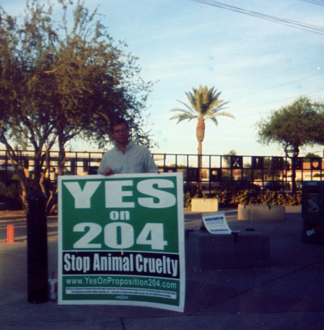"Farm Sanctuary President and Co-founder Gene Baur stands with a sign saying ""Yes on 204"""