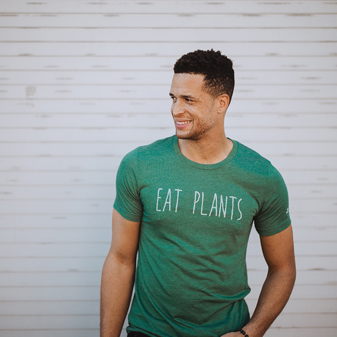 "A man wearing a green shirt that says ""Eat Plants"""