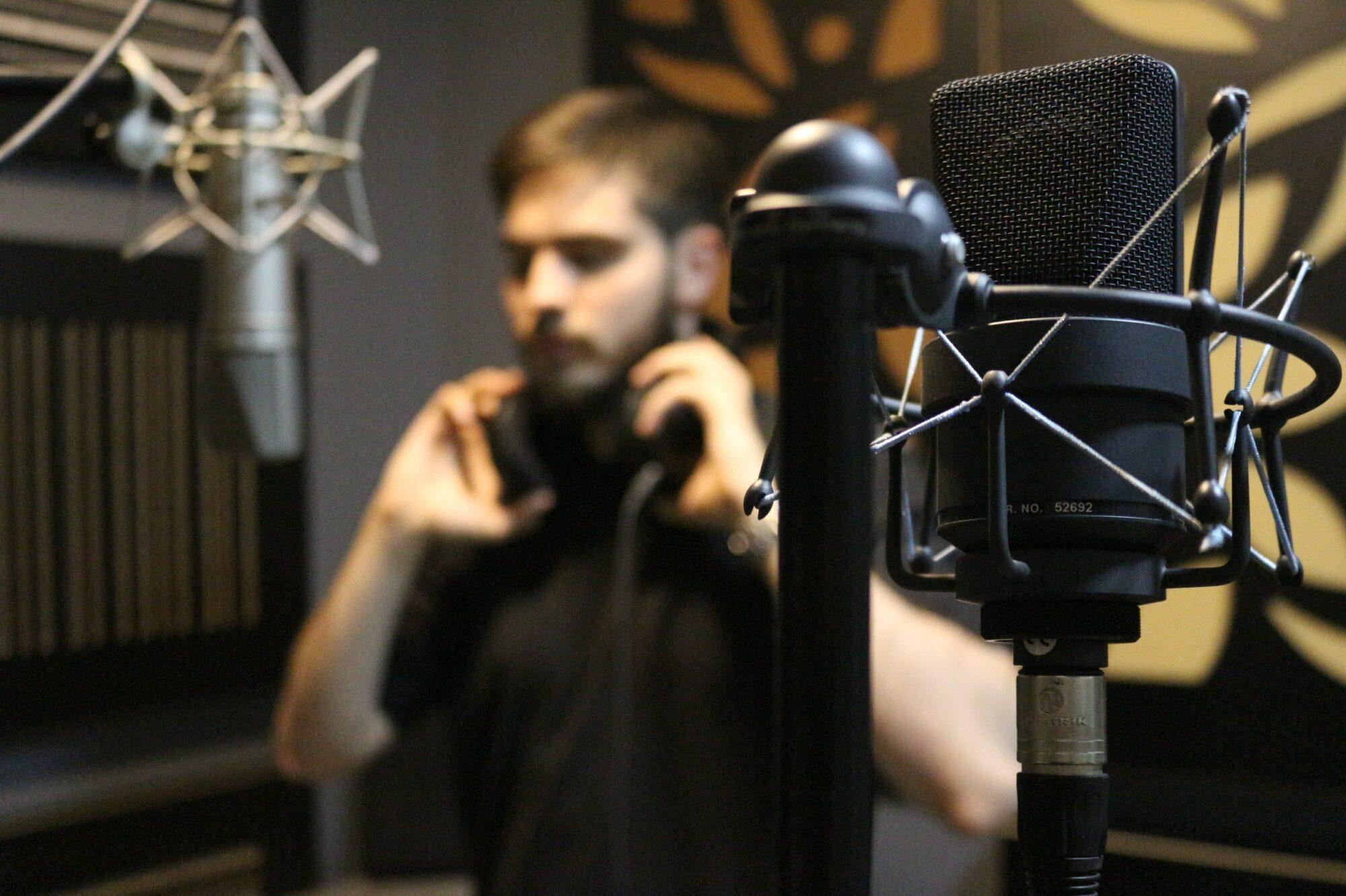 Recording_artist_man_holding_headphones_in_the_studio