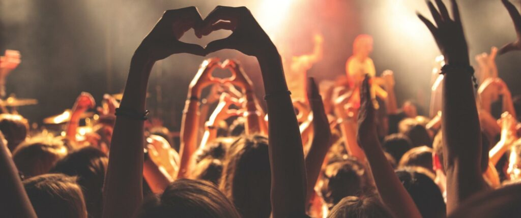 Hand Making a Heart Shape in a Crowded Concert