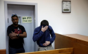 The teen arrested for JCC bomb threats covers his face at a hearing.