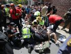 Charlottesville  First aid workers help those hurt by a car deliberately plowing into a crowd demonstrating against white supremacists marching.