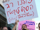 At a gathering opposing the Israeli rabbinate's decision to not consider Rabbi Haskel Lookstein's conversions valid, a protester holds a sign proclaiming solidarity with Lookstein in Hebrew and criticizing him for his RNC speech in English. Famed refusenik Nathan Sharansky stands in the foreground.