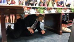 Surprise! Sen. Al Franken hides under a table to surprise Sen. Cory Booker on his birthday.