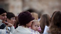 A woman holds her baby as members of the religious group ?Women of the Wall? pray at the Western Wall on April 11, 2013.