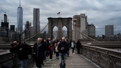 Tourists walk across the Brooklyn Bridge in New York on May 5, 2016. / AFP / Getty Images