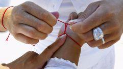 Woman tying a Kabbalah bracelet.