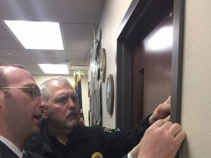 Rabbi Adam Scheier and Chief William Dial affix a mezuzah to a door in the Whitefish police station.