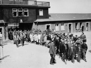 Saved: Child survivors exit Buchenwald?s main gate after liberation, escorted by American soldiers.