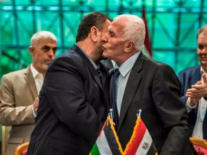 Fatah's Azzam al-Ahmad (R) and Saleh al-Aruri (L) of Hamas kiss after signing a reconciliation deal in Cairo on October 12, 2017, as the two rival Palestinian movements ended their decade-long split following negotiations overseen by Egypt.