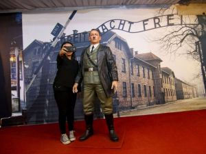 An Indonesian woman takes a selfie with a life-size wax sculpture of Adolf Hitler against a backdrop of the Auschwitz concentration camp at a museum in Yogyakarta.