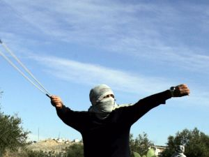 A Palestinian youth throws stones at Israeli soldiers following a demonstration in the West Bank village of Nilin, near Ramallah, on January 21, 2009.