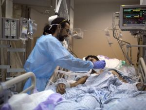 An Israeli medical staff tends to a Syrian young boy, who was wounded in the ongoing violence in Syria, as he lies on a hospital bed during his treatment at Ziv hospital in Safed.