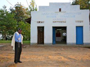 Abayudaya Jew Seth Yonadav on the phone in front of Moses Synagogue, Nabugoye Village, Mbale, Uganda. August 2013.