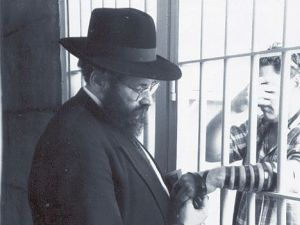 Keeping Kosher: Rabbi Sholom Lipskar wraps tefillin with a prisoner in a Florida jail.