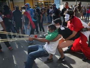 Protesters sling stones at Venezuelan national guard troops during an anti-government demonstration in Caracas, Venezuela.