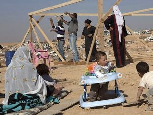 Rebuilding: Members of the Al-Turi family from the village of Al-Arakib rebuild a makeshift home in December after it was demolished for the eighth time by the Israeli government.