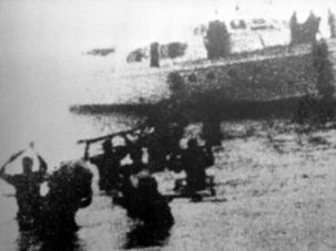 A grainy photo taken by one of Castro's band shows his men disembarking from the Granma to begin their revolution in November 1956