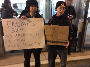 Benny Koval, at right, is one of a handful of Jews who identify as antifa activists. At a protest against President Trump's travel ban, she carries sign commemorating Anne Frank.