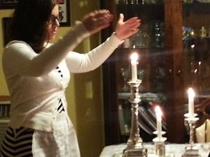 Clean Slate for Hashem: Frimet Goldberger wears the hand-embroidered cotton apron she received from her mother-in-law while lighting Sabbath candles.