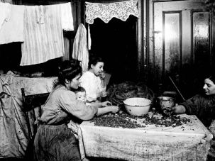 Many Faces: The kitchen served multiple roles in New York tenements in the late 19th and early 20th centuries. Here, members of an immigrant family shell nuts at their kitchen table to earn money.