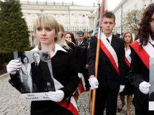 Grief: Mourners in Warsaw carry portraits of the late Polish President Lech Kaczynski and his wife, Maria.