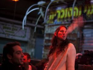 Blowing Smoke: A woman smokes a cigarette in the Mahane Yehuda market in Jerusalem.