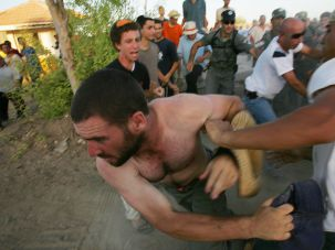 Taken by Force: A Gaza settler runs from Israeli police prior to Israel's disengagement from Gaza in 2005.