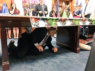 Surprise! Sen. Al Franken hides under a table to surprise Sen. Cory Booker on his birthday.