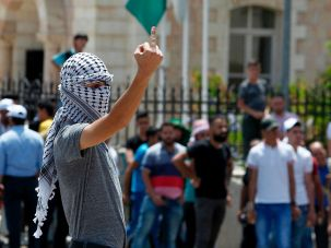 A Palestinian protester flashes his middle finger towards Israeli soldiers after Friday prayers in the West Bank city of Bethlehem on July 21.