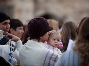 A woman holds her baby as members of the religious group Women of the Wall pray at the Western Wall on April 11, 2013.