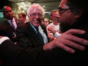 Philosopher Cornel Wes embraces Democratic presidential candidate Sen. Bernie Sanders at a watch party for the second Democratic presidential debate on Nov. 14, 2015 in Iowa.